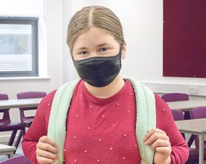 Jeune fille portant un masque de protection pour le visage noir, avec un sac à dos vert, dans une salle de classe