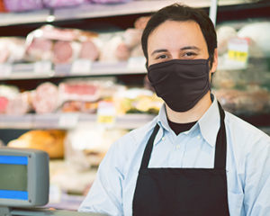 Homme à la caisse dans une épicerie, portant un masque de protection pour le visage noir