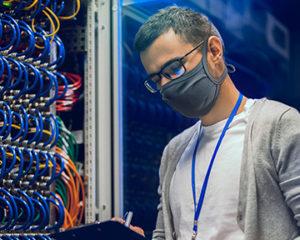Homme ingénieur de réseaux portant un masque de protection pour le visage noir et des lunettes, avec un bloc note dans les mains, prenant des notes