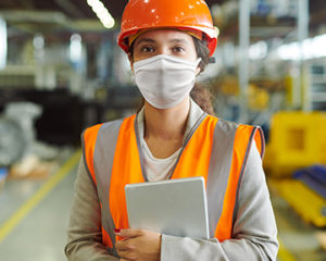 Woman wearing a white protective face mask in a warehouse with a protective helmet